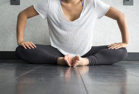 Young dancer pressing legs down into butterfly position to stretch hips in the studio