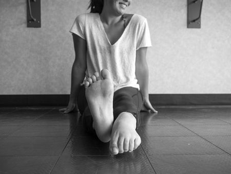 Black and white version of Smiling dancer warming up her feet with alternating pointing and flexing
