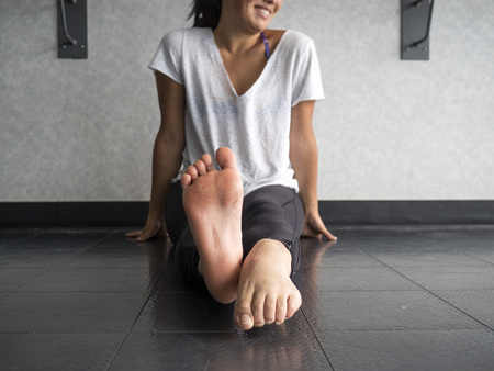 Smiling dancer warming up her feet with alternating pointing and flexing