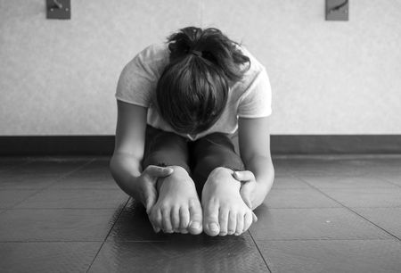 Black and white version of Young woman performing and sit and reach to stretch hamstrings and increase flexibility