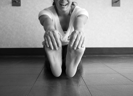 Black and white version of Smiling active woman grabbing her feet to stretch hamstrings in the studio Stock Photo