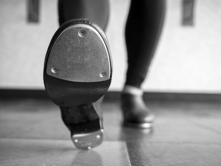 Black and white version of Heel toe in tap shoes in dance class