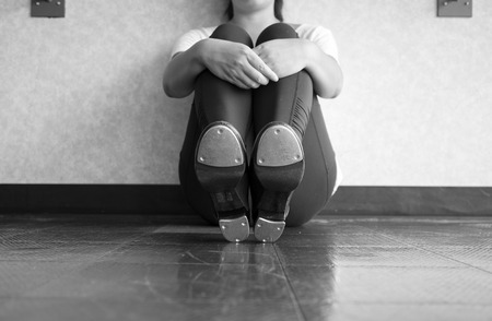 Black and White Version of Tap dancer sitting down, showing taps, and holding her legs 版權商用圖片