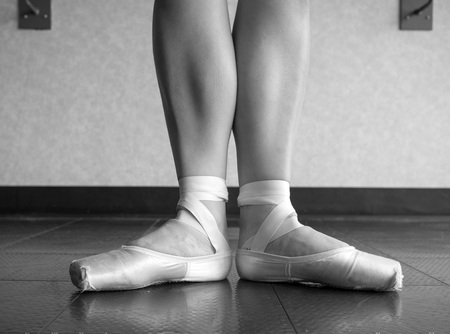 Black and white version of Ballerina in Ballet first position in ballet pointe shoes and bare legs