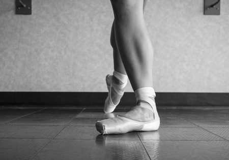 Black and white version of Ballet dancer showing off her pointe shoes standing in classical position 版權商用圖片
