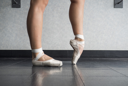 Ballerina warming up her feet in her pointe ballet shoes before class
