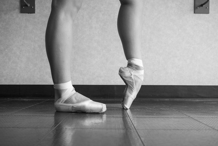 Black and white version of Ballerina warming up her feet in her pointe ballet shoes before class 版權商用圖片