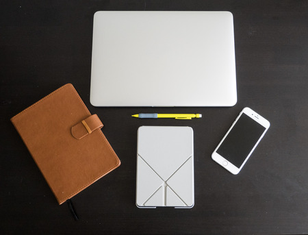 Student and worker desktop workspace layout including a laptop, smartphone, journal, tablet and pencil