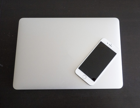 New age technology- isolated laptop and smartphone cell on a black table background
