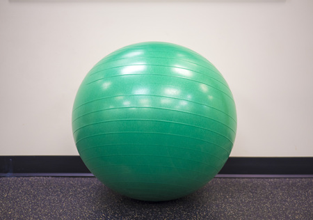 Green exercise ball on an isolated background at the gym Stock Photo