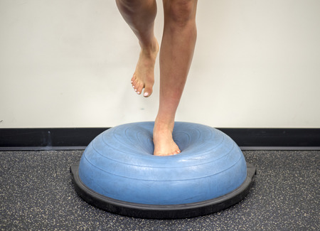 Young female standing on a bosu ball for a workout 版權商用圖片