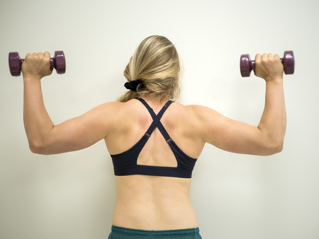 Strong white female doing exercises working on her biceps and shoulder muscles with weights