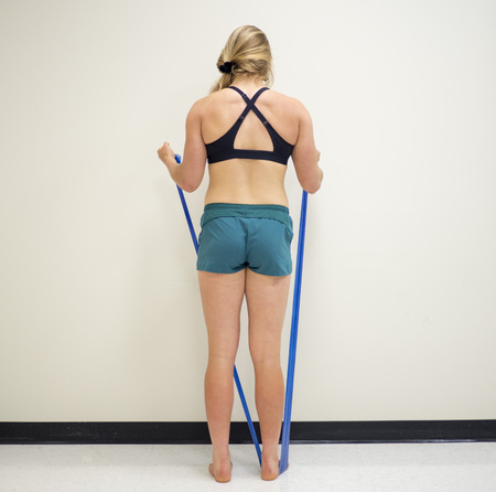 Back view of an athletic female using a theraband resistance band for exercise Stock Photo