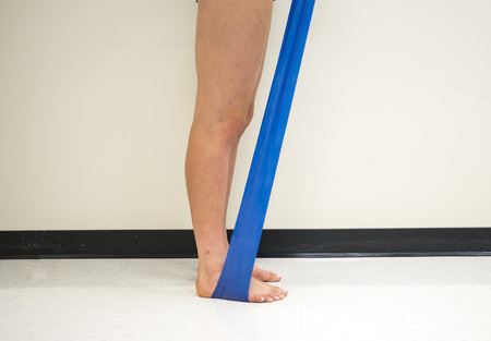 Standing female pulling up on a resistance band underneath her feet