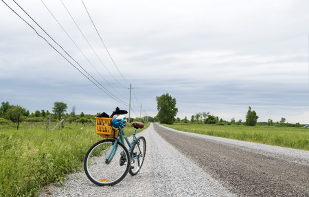 Bike with a basket parked on the side of a gravel road