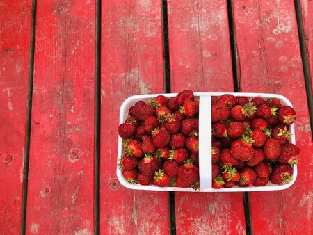 Fresh picked juicy Strawberries in a basket on a red wood background