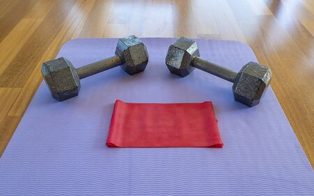 Close up of Dumbbells and Exercise band on a Yoga Mat for a Home workout