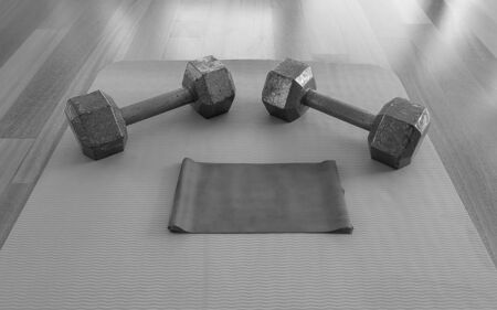 Black and white version of Close up of Dumbbells and Exercise band on a Yoga Mat for a Home workout Reklamní fotografie