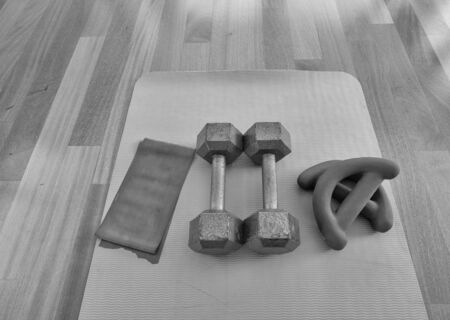 Black and white version of Overhead view of a pair of dumbbells, theraband exercise bands, and a yoga mat on hardwood floor