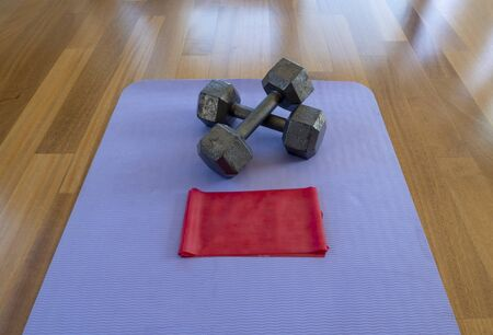 Crossed Dumbbells and Exercise band on a Yoga Mat for a Home workout