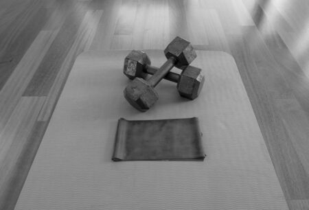 Black and white version of Crossed Dumbbells and Exercise band on a Yoga Mat for a Home workout