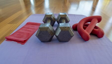 Close up of a pair of dumbbells, theraband exercise bands, and a yoga mat on hardwood floor 版權商用圖片 - 129072103