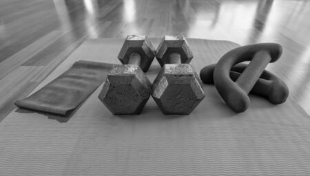 Close up of a pair of dumbbells, theraband exercise bands, and a yoga mat on hardwood floor