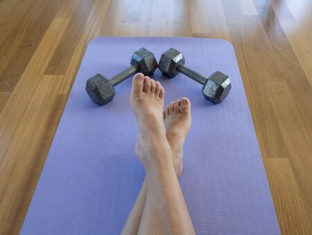 Crossed legs Feet and Dumbbells after a home workout on a yoga mat 版權商用圖片