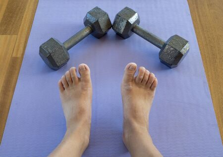 Feet and Dumbbells after a home workout on a yoga mat