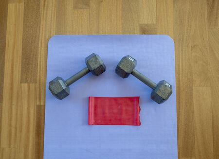 Dumbbells and Exercise band on a Yoga Mat for a Home workout
