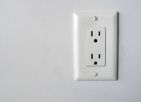 Isolated North American power outlet plug in socket on a white wall background Type B style