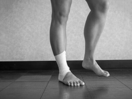 Black and white version of Athlete performing mobility exercises on injured ankle with a tape job