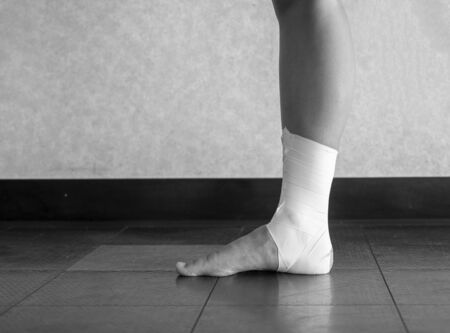 Black and white version of Sprained ankle all taped up 版權商用圖片 - 129074184