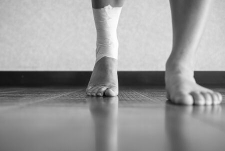 Black and white version of Athlete walking forward with an ankle injury and ankle tape job Reklamní fotografie