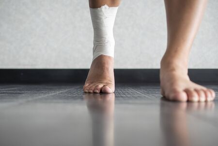 Athlete walking forward with an ankle injury and ankle tape job