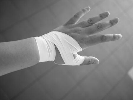Black and white version of Athlete with a taped thumb