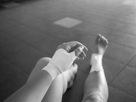 Black and white version of The injured athlete- athlete with thumb and ankle injuries and tape jobs