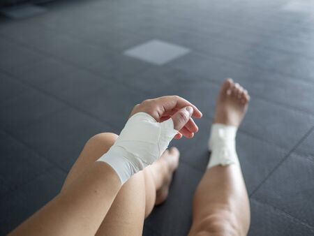 The injured athlete- athlete with thumb and ankle injuries and tape jobs