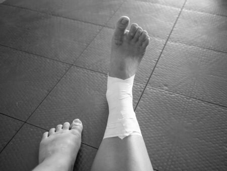 Black and white version of Perspective of an athlete looking at her taped ankle sprain