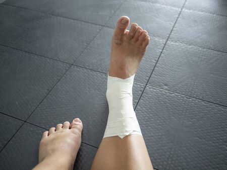 Perspective of athlete looking at her taped ankle sprain
