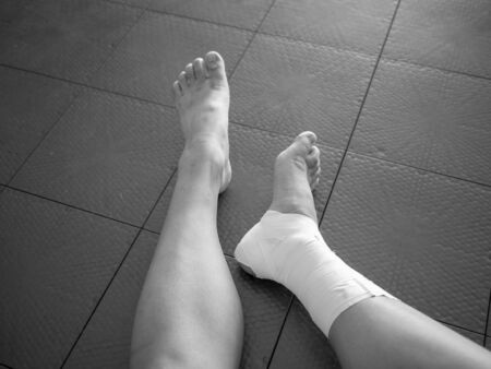 Black and white version of Athlete staring at her injured ankle