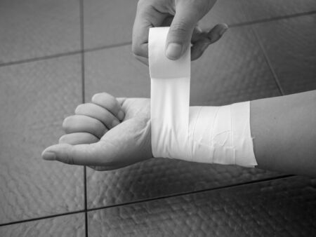 Black and white version of Athlete taping her wrist for injury and support Reklamní fotografie