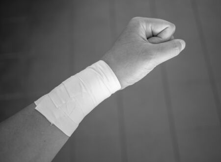 Black and white version of Making a fist with a wrist tape job