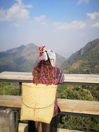 Akha tribe woman costume sitted on the bench with mountain view