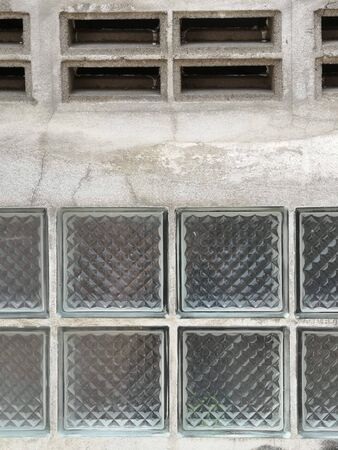 The wall has glass blocks and vents on the top.
