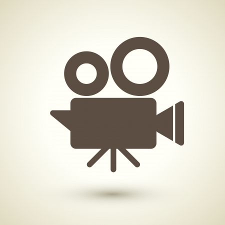 mass media: retro style cinema camera icon isolated on brown