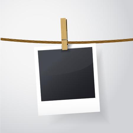 instant film transfer: blank photo frame on rope over white background