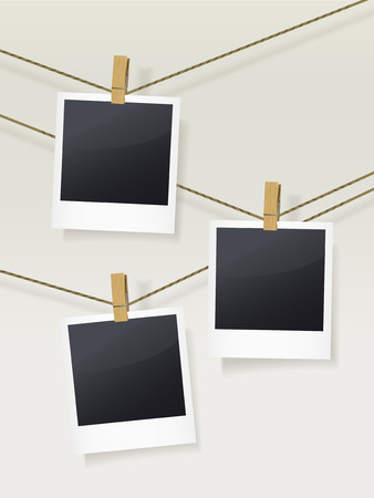 dark room: blank photo frames on clotheslines isolated on beige
