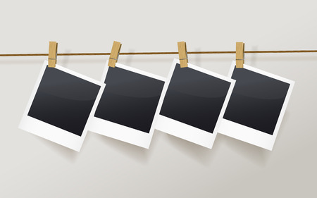 dark room: blank photo frames on a clothesline isolated on white
