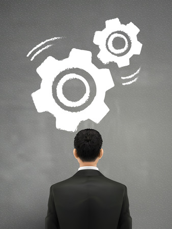 businessman looking at gears sketch over grey